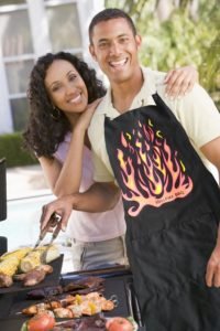 smiling woman and man wearing apron at BBQ