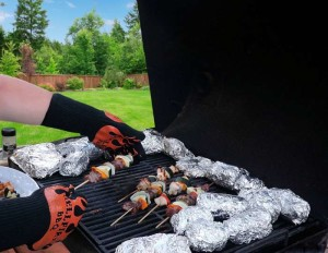 BBQ grill with several potatoes in foil and gloved hand