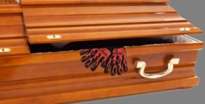 gloves emerging from full-sized coffin