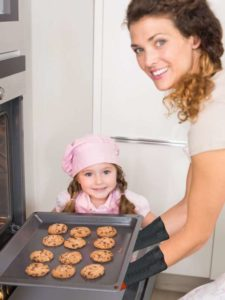 woman and small girl in kitchen taking hot cookies from oven