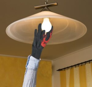 hand in glove changing hot light bulb
